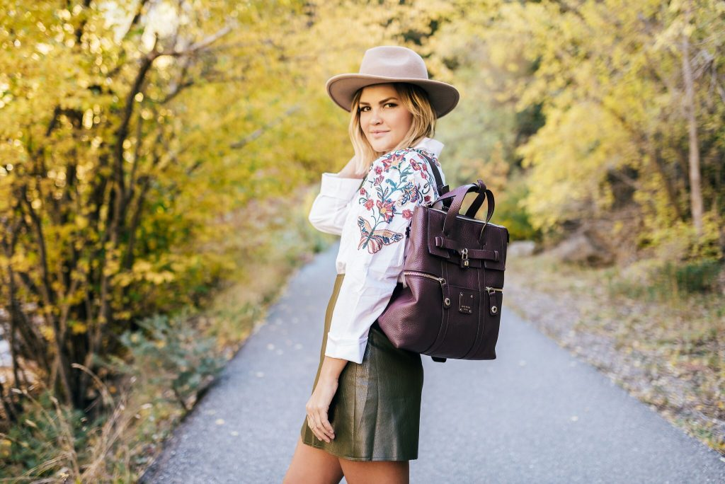Green mini skirt and embroidered blouse and Henri Bendel Jetsetter Backpack
