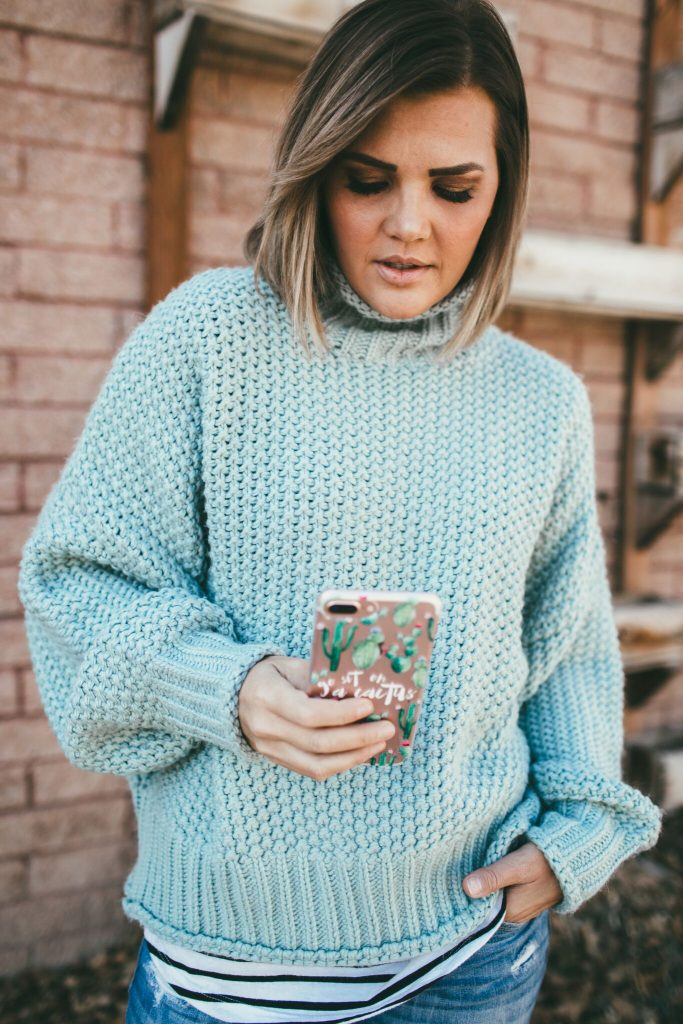 green chunky knit sweater and cactus phone case